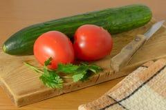 Pomodori e cetrioli sulla scheda di taglio Immagini Stock Libere da Diritti