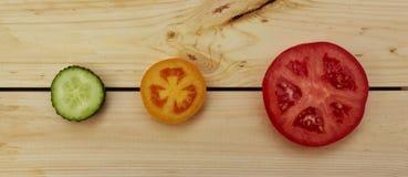 Pomodori e fette del cetriolo Fotografia Stock