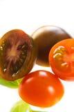 Pomodori e foglie del basilico isolate su bianco Immagini Stock