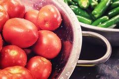 Pomodori e jalapeni in inossidabile fotografia stock