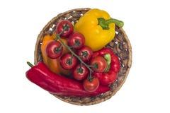 Pomodori e merce nel carrello multicolore dei peperoni su fondo isolato Immagini Stock