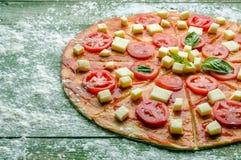Pomodori e mozzarella sulla pasta cruda della pizza Fotografie Stock Libere da Diritti