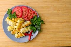 Pomodori e patate spezia Su un piatto di ceramica rustic Fotografia Stock Libera da Diritti