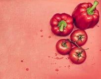 Pomodori e pepe maturi sul tagliere rosso con le gocce di acqua Immagini Stock
