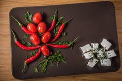 Pomodori e peperoni con formaggio e le erbe su un piatto scuro Immagini Stock Libere da Diritti