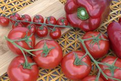 Pomodori e peperoni su un fondo di legno e su una stuoia della paglia Fotografie Stock Libere da Diritti