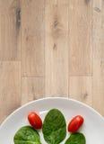 Pomodori e spinaci sul piatto bianco Immagine Stock Libera da Diritti