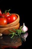 Pomodori ed aglio in zolla di legno su backg nero fotografie stock