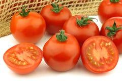 Pomodori freschi e un taglio uno Fotografia Stock Libera da Diritti