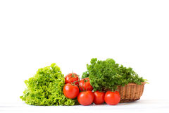 Pomodori freschi ed erbe differenti in un canestro di vimini Immagini Stock