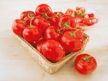 Pomodori freschi in un cestino di vimini sulla tabella Immagini Stock Libere da Diritti