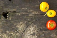 Pomodori gialli e rossi su un fondo di legno fotografia stock libera da diritti