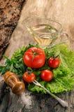 Pomodori, insalata, olio sul bordo di legno invecchiato Fotografie Stock