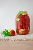 Pomodori inscatolati sulla tavola di legno Fotografia Stock