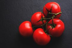 Pomodori italiani maturi sul nero Immagine Stock