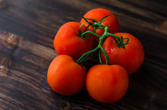 Pomodori maturi della vite organica sulla tavola di legno Immagine Stock
