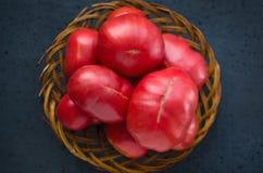 Pomodori maturi molto grandi in un grande piatto di legno di vimini su un fondo nero fotografie stock libere da diritti