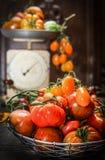 Pomodori organici freschi dell'azienda agricola sopra le scale di legno scure dell'annata e del fondo Fotografie Stock