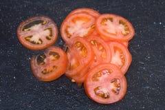 Pomodori pastosi sottilmente affettati sul tagliere nero Fotografie Stock Libere da Diritti