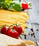 Pomodori per la salsa di spaghetti sulla tavola di legno blu Immagini Stock