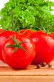 Pomodori, quattro spezie e lattuga bagnati freschi a bordo di di legno Fotografia Stock