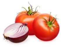 Pomodori rossi con le foglie verdi e la metà della cipolla non sbucciata Fotografie Stock Libere da Diritti