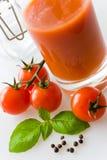 Pomodori rossi freschi con la foglia ed il succo del basilico Fotografie Stock