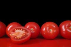 Pomodori rossi freschi di Roma sulla tavola rossa e sul fondo nero, copia Fotografia Stock
