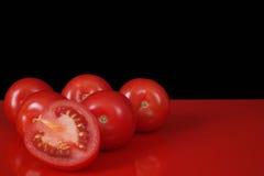 Pomodori rossi freschi di Roma sulla tavola rossa e sul fondo nero, copia Immagine Stock