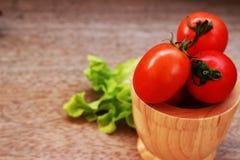 Pomodori rossi freschi in una ciotola marrone disposta su un tabl di legno marrone Fotografie Stock Libere da Diritti