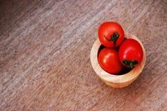 Pomodori rossi freschi in una ciotola marrone disposta su un tabl di legno marrone Immagini Stock Libere da Diritti