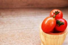 Pomodori rossi freschi in una ciotola marrone disposta su un tabl di legno marrone Fotografie Stock