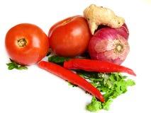 Pomodori rossi, peperoncini rossi rossi, zenzero e cipolla su fondo bianco Fotografia Stock