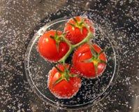 Pomodori rosso ciliegia in acqua immagini stock libere da diritti