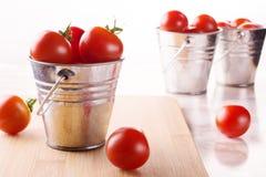 Pomodori su un piccolo secchio su un fondo bianco Immagine Stock