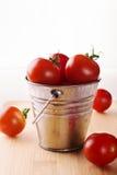 Pomodori su un piccolo secchio su un fondo bianco Immagini Stock