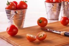 Pomodori su un piccolo secchio su un fondo bianco Fotografie Stock Libere da Diritti