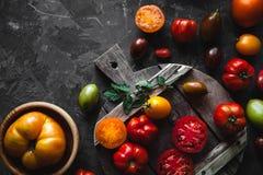 Pomodori sul vecchio bordo, taglio e con i verdi, alimento sano, verdure fotografia stock libera da diritti
