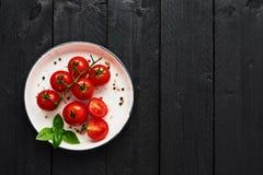 Pomodori in un piatto con sale himalayano, pepe e basilico sul bla fotografie stock
