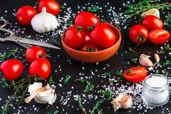 Pomodori in un piatto su un fondo nero fotografie stock