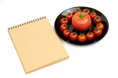 Pomodori in una banda nera isolata su fondo bianco vicino ad un blocco note Composizione dei pomodori rossi in un piatto su un ba immagini stock libere da diritti