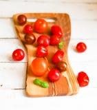 Pomodori variopinti a bordo su fondo di legno Fotografia Stock