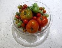 Pomodori variopinti organici freschi assortiti in una ciotola di vetro Immagini Stock