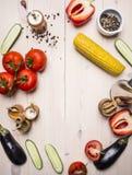 Pomodori vegetariani di concetto, intero pepe, peperone dolce rosso, mais, cetrioli e Cl rustico di legno di vista superiore del  Fotografia Stock