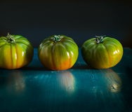Pomodori verdi sul blu dipinto di legno fotografie stock
