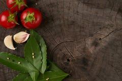 Pomodoro, aglio e foglia di alloro succosi su una tavola di legno Immagini Stock