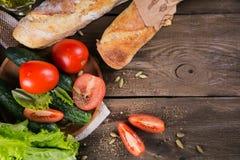 Pomodoro, cetriolo, lattuga, baguette, olio d'oliva e spezie fotografia stock