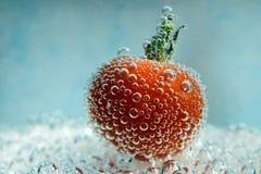 Pomodoro ciliegia con le bolle subacquee Fotografia Stock