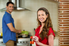 Pomodoro ciliegia ed uomo della tenuta della donna che cucinano sulla stufa Fotografia Stock Libera da Diritti