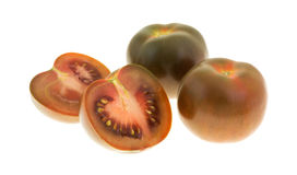 Pomodoro di Brown affettato a metà con intera frutta Immagine Stock Libera da Diritti